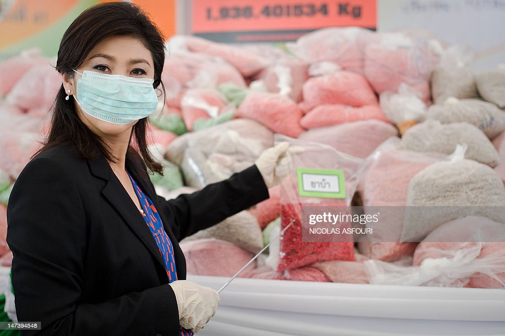 Thailand's Prime Minister Yingluck Shinawatra stands in front of bags of methamphetamine tablets during the 41th Destruction of Confiscated Narcotics ceremony in Ayutthaya province, about 80 kms (50 miles) north of Bangkok on June 29, 2012. Thai police on June 29 incinerated more than 225 million USD of seized drugs -- including 21 million amphetamine tablets -- as the kingdom ramps up its efforts to stem the flow of narcotics in the country. AFP PHOTO / Nicolas ASFOURI