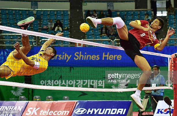 Thailand's Suriyan Peachan challenges for the ball with Malaysia's Mohamad Fadzli Bin Muhammad Roslan in the men's team sepaktakraw semifinal match...