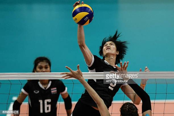 TOPSHOT Thailand's Thinkaow Pleumjit spikes the ball against Philippines player Santiago Alyja Daphne Antonio during their volleyball women's...
