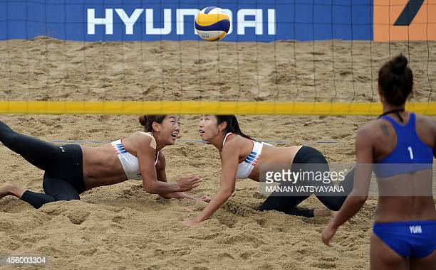 Thailand's Yupa Phokongploy watches as South Korea's Lee Una and Yoon Hyesuk return a volley during the womens beach volleyball preliminary round...