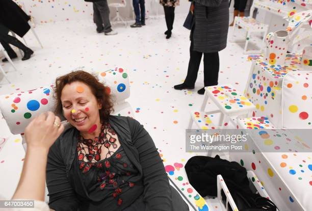 Thais Austin has stickers put on her face by Bhavna Sharma in the Obliteration Room at the Yayoi Kusama Infinity Mirrors exhibit at the Hirshhorn...