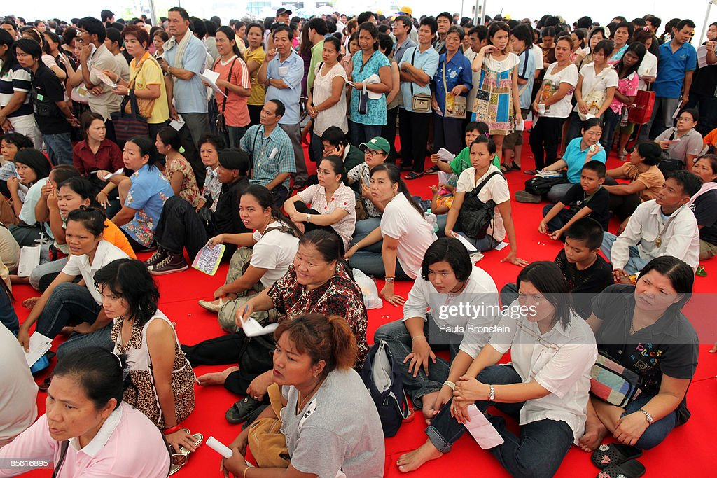 Thais wait for hours to receive a government check of 2000-baht ($57.00 US) at the city hall March 26, 2009 in Bangkok, Thailand. The pay out is being given to stimulate an economy battered by the global financial crisis. Eight million Thais have been unemployed since September 1, 2008, and in total there are 9.4 million people who make less than 15000 baht per month and are eligible for the cash hand-out. Today 20,000 red-shirted protesters surrounded the prime minister's office demanding the government resign. The pro-Thaksin supporters claim that Prime Minister Abhisit Vejjajiva government came to power through illegal means and are demanding elections.
