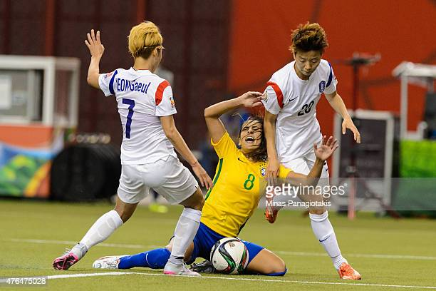 Thaisa of Brazil gets caught between Jeon Gaeul and Kim Hyeri of Korea Republic during the 2015 FIFA Women's World Cup Group E match at Olympic...