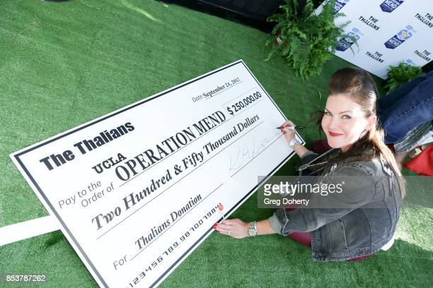 Thalian Board Member and Actress Kira Reed Lorsch signs the $250K dollar donation check at the UCLA Operation Mend 10 year anniversary at the home of...