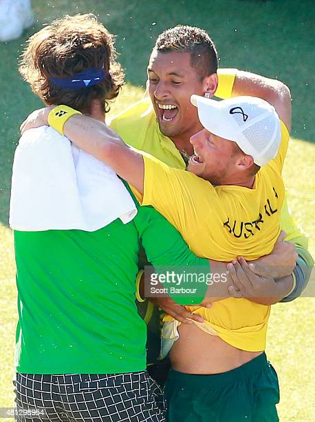 Thanasi Kokkinakis and Nick Kyrgios run on court to congratulate teammate Lleyton Hewitt of Australia as he celebrates winning the reverse singles...