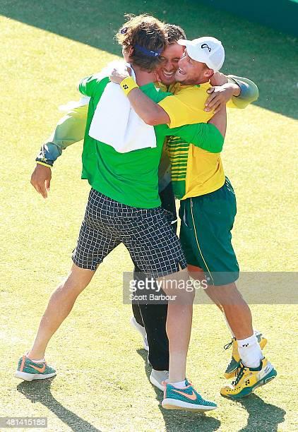 Thanasi Kokkinakis and Nick Kyrgios run on court to congratulate teammate Lleyton Hewitt of Australia as he celebrates winning the reverse singles...