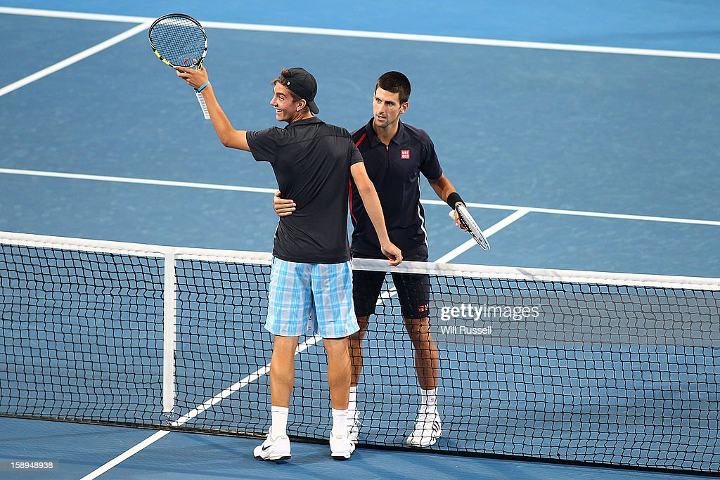 Thanasi Kokkinakis of Australia and <a gi-track='captionPersonalityLinkClicked' href=/galleries/search?phrase=Novak+Djokovic&family=editorial&specificpeople=588315 ng-click='$event.stopPropagation()'>Novak Djokovic</a> of Serbia embrace while Tatjana Malek of Germany and Ana Ivanovic of Serbia play from the baselines during day seven of the Hopman Cup at Perth Arena on January 4, 2013 in Perth, Australia.