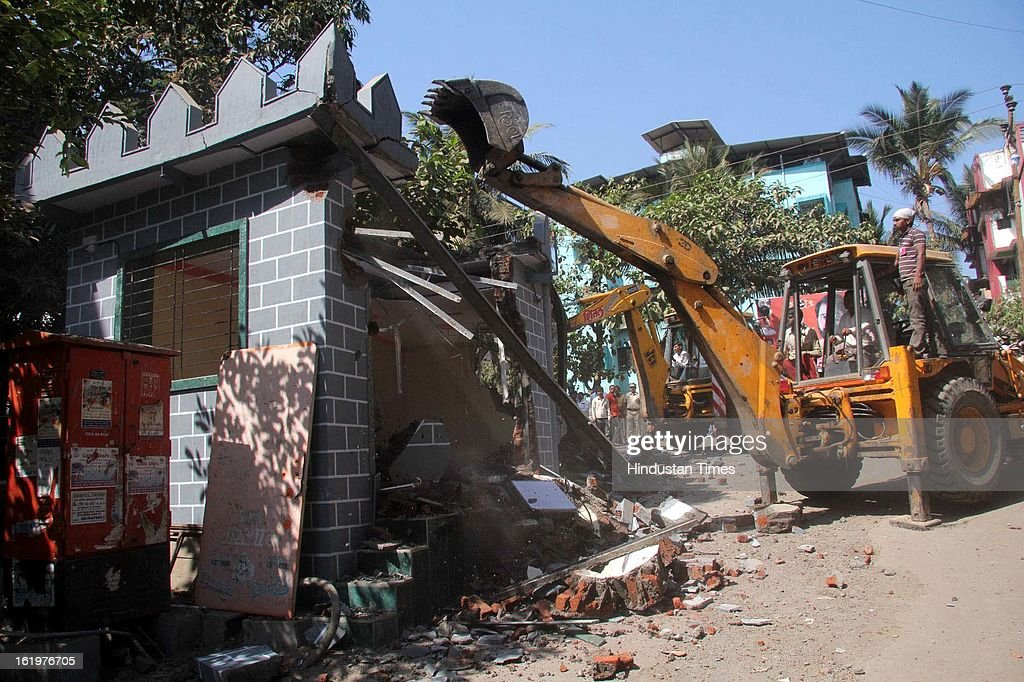 Thane Municipal Corporation officials razing unauthorised party offices of Shiv Sena and MNS parties from Kasarwadavli to Ambika Nagar under police protection following the High Court's order on February 18, 2013 in Mumbai, India.