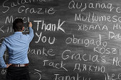 "Man in blue business short writing with chalk on blackboard the word ""Thank You"" in many languages"