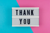 Thank you - text on a display lightbox on blue and pink bright background.