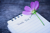 Thank You text on a white page note book with romantic white flower on wooden background.
