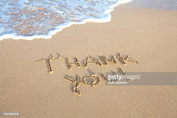 Gracias por escrito en la arena en la playa