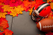 Thanksgiving american football game concept with copy space, a generic helmet and ball on the pavement surrounded by fall foliage leafs in autumn