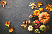 Thanksgiving day or seasonal autumnal background with pumpkins and fallen leaves on stone background. Copy space for text