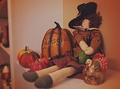 Pilgrim doll, ceramic turkey and other seasonal decorations sitting on a fireplace mantle