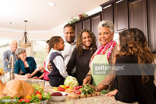 Thanksgiving:  Multi-ethnic family, friends gather in kitchen to prepare meal.