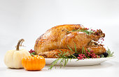 """Thanksgiving pepper roasted turkey garnished with blackberry, pink peppercorn, and mini pumpkins on white.""""n"""