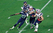 Tharold Simon of the Seattle Seahawks corrals Julian Edelman of the New England Patriots during the game at the University of Phoenix Stadium on...