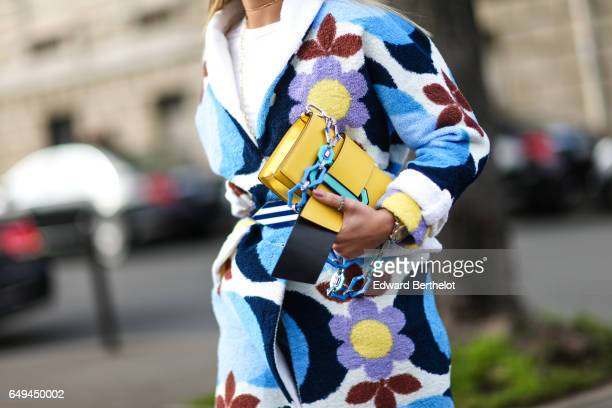 Thassia Naves wears a flower print coat a white top blue jeans a yellow bag and blue heels outside the Miu Miu show during Paris Fashion Week...