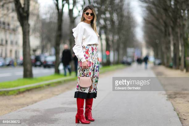 Thassia Naves wears a white ruffled top a flower print skirt a pink bag and red boots outside the Moncler Gamme Rouge show during Paris Fashion Week...