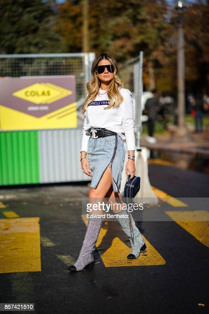 Thassia Naves wears a white top a blue skirt boots outside Chanel during Paris Fashion Week Womenswear Spring/Summer 2018 on October 3 2017 in Paris...