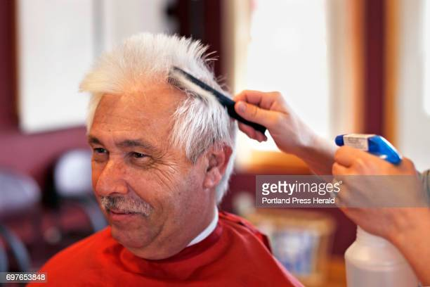 That Moment Jim Dolloff sits in a barber chair while cosmetologist Leanne Jackson wets his hair at Cuttin' It Close barbershop