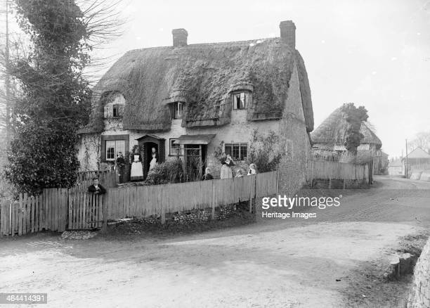 Thatched cottage with its inhabitants standing outside Ramsbury Wiltshire c1860c1922
