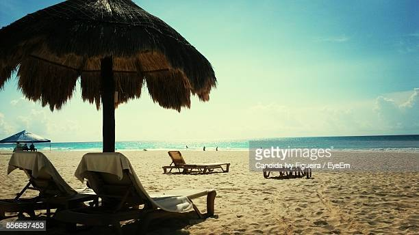 Thatched Roof And Lounge Chairs On Beach