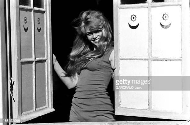 Brigitte Bardot Le 10ème Festival de Cannes 1957 se déroule du 2 au 17 mai attitude souriante de Brigitte BARDOT dans l'encadrement d'une fenêtre