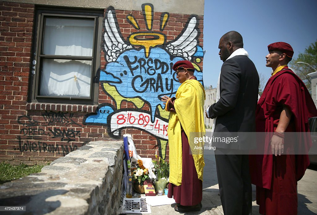 The 12th Gyalwang Drukpa (L), the Buddhist leader of South Asia (Nepal, India, Bhutan), says a prayer at the spot where Freddie Gray was arrested May 7, 2015 in Baltimore, Maryland. Gyalwang Drukpa was accompanied by the Rev. Jamal Bryant (2nd L) of the Empowerment Temple to tour the Baltimore neighborhoods affected by the recent unrest.