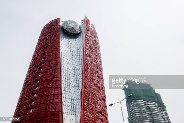 The 13 Hotel developed by 13 Holdings Ltd left stands next to a residential building under construction in the Coloane Village district of Macau...