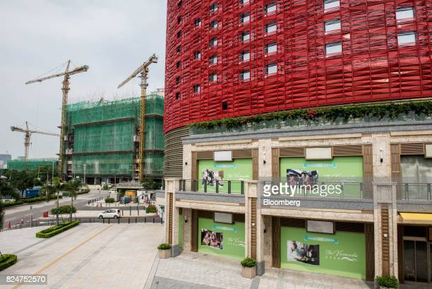 The 13 Hotel developed by 13 Holdings Ltd right stands in front of a construction site in the Coloane Village district of Macau China on Monday July...