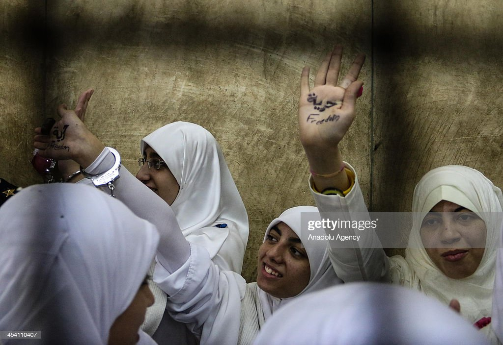 The 14 Egyptian women who were sentenced to 11-year jail terms for taking part in pro-Morsi protest last month, show their palms as they stand in the defendants' cage during their appeal hearing in a courtroom on December 7, 2013 in Alexandria, Egypt. An Egyptian court on Saturday slapped suspended one-year jail terms against 14 female supporters of Mohamed Morsi. Fourteen women, most of whom are in their early 20s, have been sentenced to 11 years in prison each for 'blocking roads' and 'belonging a banned organization' the latter charge a reference to the Muslim Brotherhood, the group from which Morsi hails.