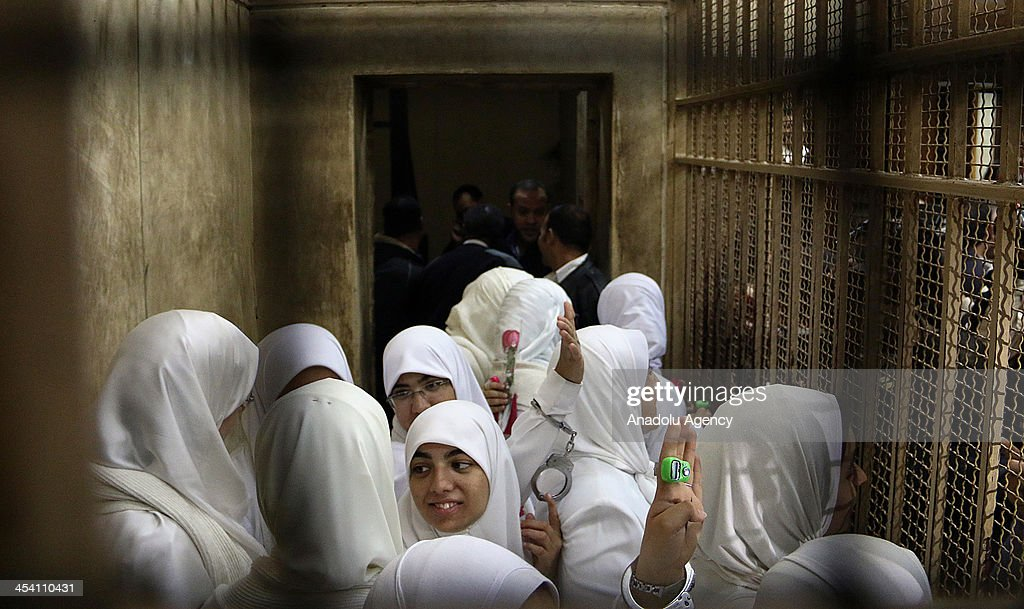 The 14 Egyptian women who were sentenced to 11-year jail terms for taking part in pro-Morsi protest last month, flash Rabia sign as they stand in the defendants' cage during their appeal hearing in a courtroom on December 7, 2013 in Alexandria, Egypt. An Egyptian court on Saturday slapped suspended one-year jail terms against 14 female supporters of Mohamed Morsi. Fourteen women, most of whom are in their early 20s, have been sentenced to 11 years in prison each for 'blocking roads' and 'belonging a banned organization' the latter charge a reference to the Muslim Brotherhood, the group from which Morsi hails.