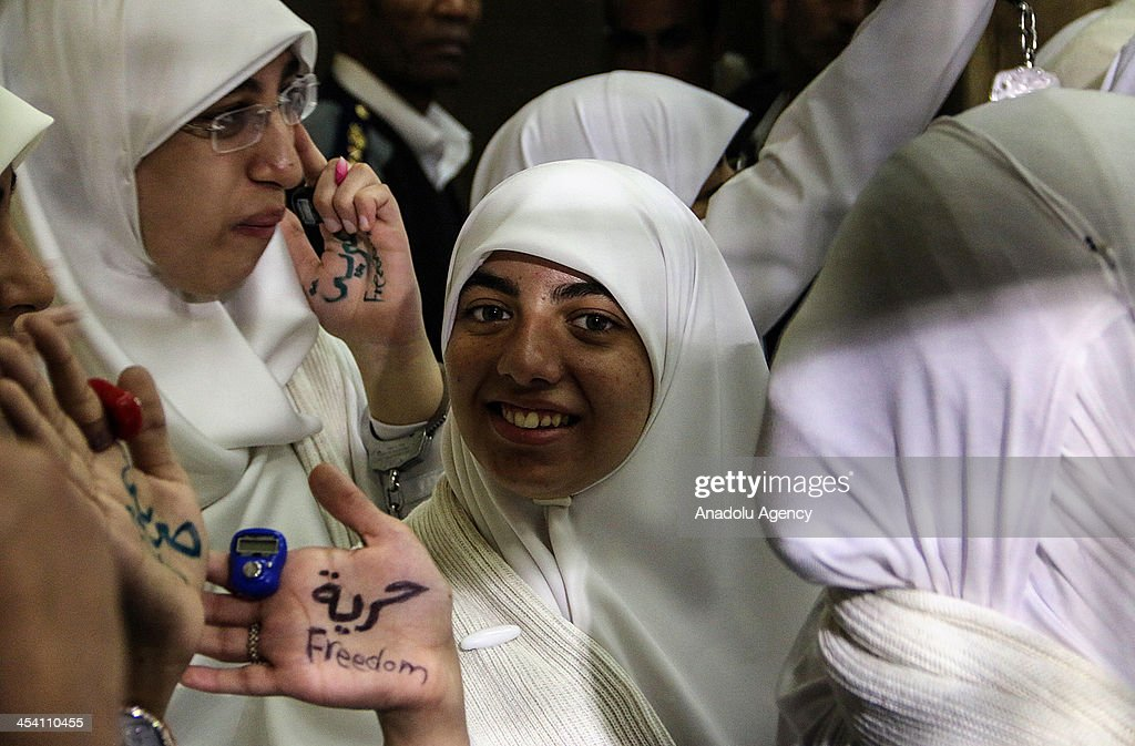 The 14 Egyptian women who were sentenced to 11-year jail terms for taking part in pro-Morsi protest last month, stand in the defendants' cage during their appeal hearing in a courtroom on December 7, 2013 in Alexandria, Egypt. An Egyptian court on Saturday slapped suspended one-year jail terms against 14 female supporters of Mohamed Morsi. Fourteen women, most of whom are in their early 20s, have been sentenced to 11 years in prison each for 'blocking roads' and 'belonging a banned organization' the latter charge a reference to the Muslim Brotherhood, the group from which Morsi hails.