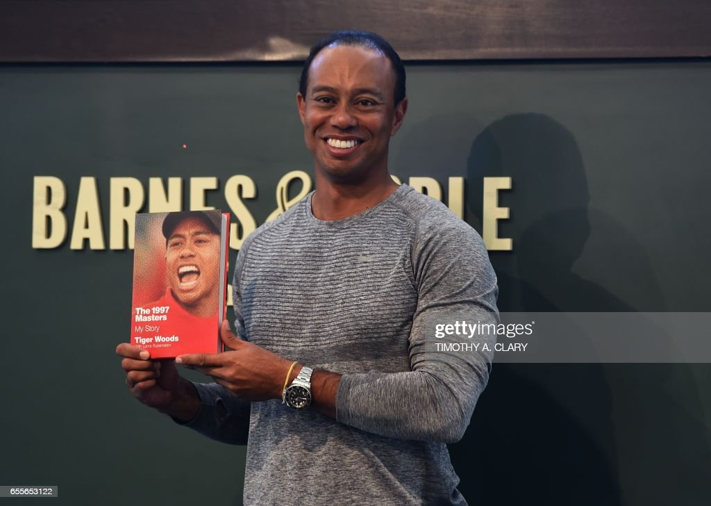 TOPSHOT - The 14-time major champ golfer Tiger Woods holds a copy of his new book 'The 1997 Masters: My Story' before his booking signing at Barnes & Noble's Union Square in New York on March 20, 2017. /