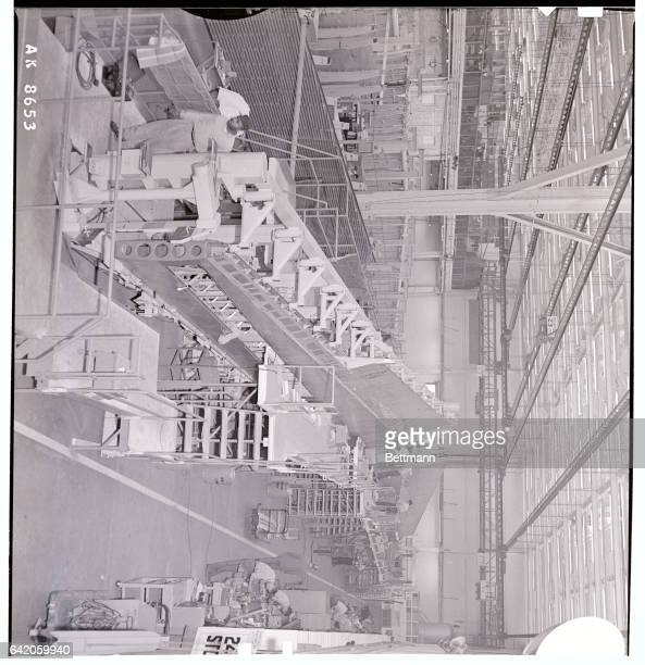 The 150 foot long wing for the new Super Constellation nears completion at the Burbank plant of Lockheed Workmen install the machined skin panels as...