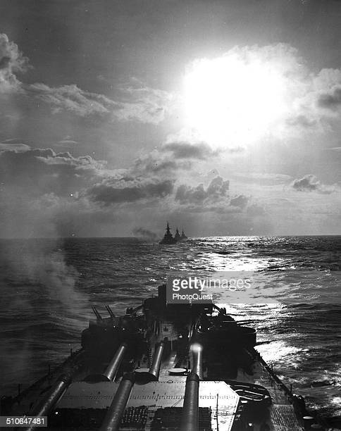 The 16inch guns of her main battery and 40mm antiaircraft batteries silhouetted by the weak rays of earlymorning sunlight the Navy battleship SOUTH...