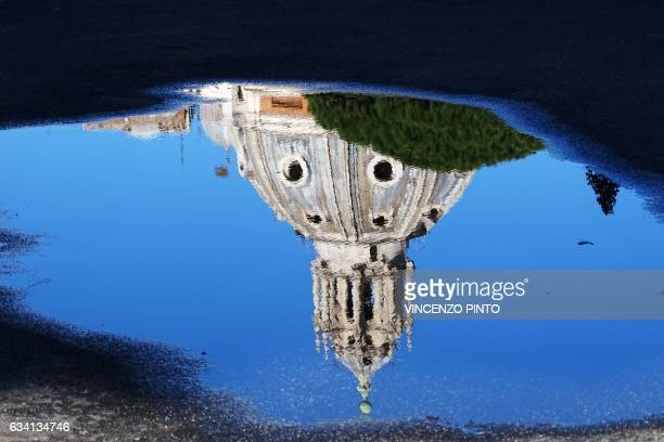 TOPSHOT The 16thcentury Santa Maria di Loreto church is reflected in a puddle in Rome's central Piazza Venezia Square on February 7 2017 / AFP PHOTO...