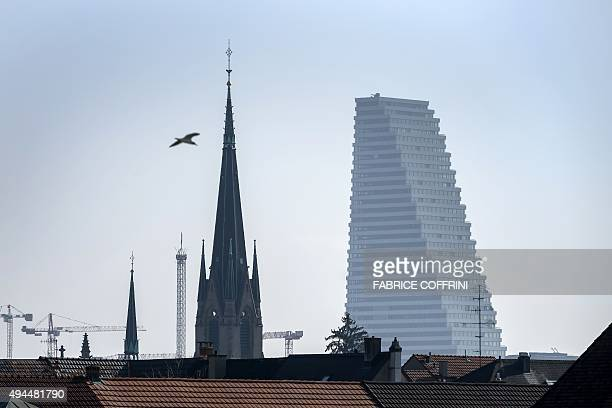 The 178 meters hight 'Building 1' of pharmaceutical giant company Roche is seen behind a church on October 27 2015 in Basel 'Building 1' designed by...