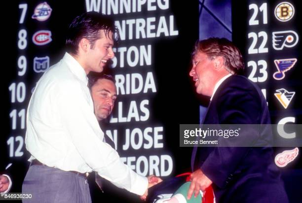 The 18th pick of the 1995 NHL Draft Petr Sykora shakes hands with the Director of Scouting for the New Jersey Devils David Conte as NHL commissioner...