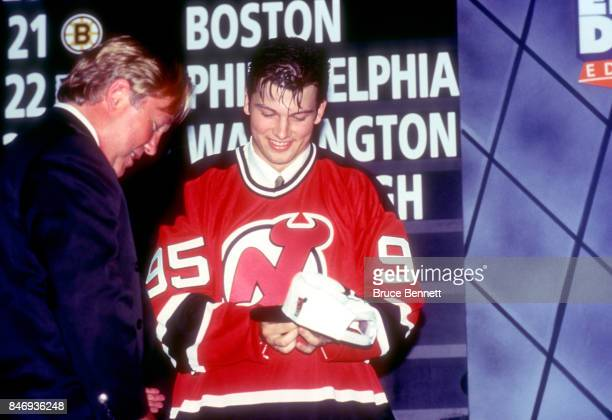 The 18th pick of the 1995 NHL Draft Petr Sykora tries on his jersey and hat as Director of Scouting for the New Jersey Devils David Conte stands next...