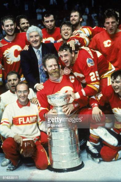 The 1989 Calgary Flames and general manager Cliff Fletcher pose for a team photo around the Stanley Cup which they have just won in a game against...