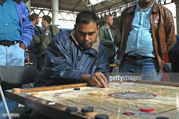 The 2003 Carrom Association International Championship winner Shaheen Miah plays a strike during an early qualifying round at Spitalfield's Market...