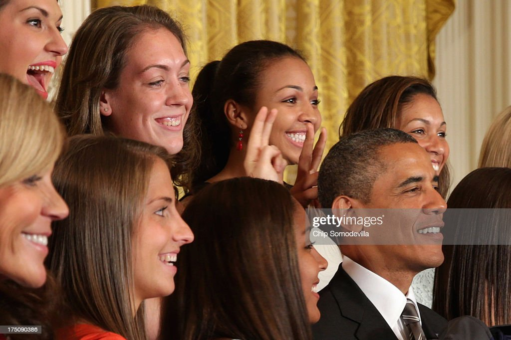 The 2013 NCAA champion University of Connecticut Huskies Women's basketball players Stefanie Dolson (L) and Kiah Stokes (C) give President Barack Obama (R) 'bunny ears' while the team poses for a photograph with the president in the East Room of the White House July 31, 2013 in Washington, DC. Obama hosted the team after they defeated the University of Louisville on April 9 to win their eighth national championship.
