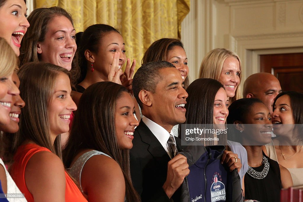 The 2013 NCAA champion University of Connecticut Huskies Women's basketball players Stefanie Dolson (L) and Kiah Stokes (3rd L) give President <a gi-track='captionPersonalityLinkClicked' href=/galleries/search?phrase=Barack+Obama&family=editorial&specificpeople=203260 ng-click='$event.stopPropagation()'>Barack Obama</a> 'bunny ears' while the team poses for a photograph with the president in the East Room of the White House July 31, 2013 in Washington, DC. Obama hosted the team after they defeated the University of Louisville on April 9 to win their eighth national championship.