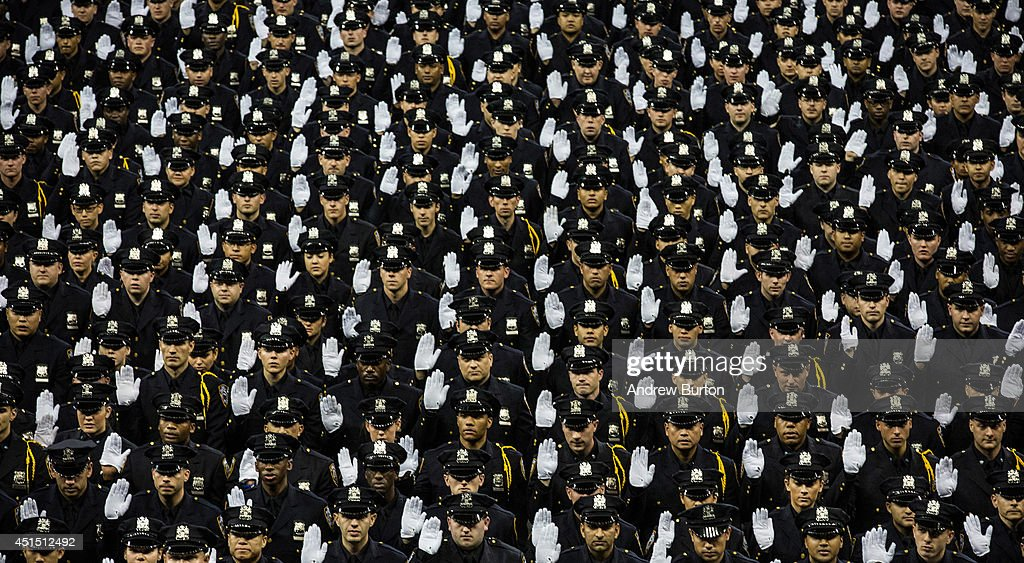 The 2014 class of the New York Police Department raise their hands while taking an oath at the NYPD graduation ceremony on June 30 2014 at Madison...