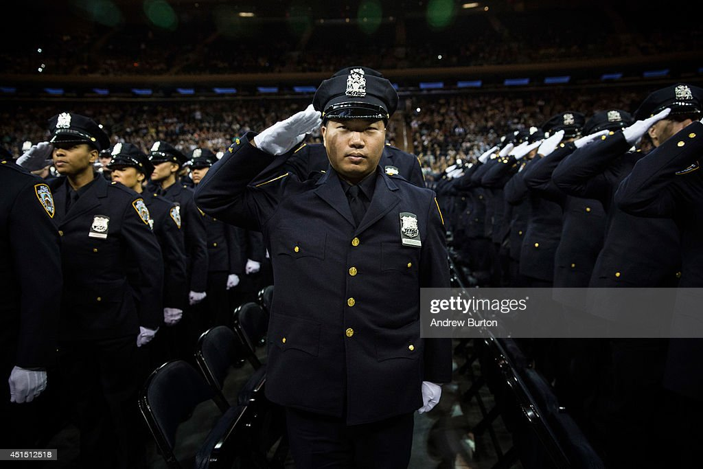 The 2014 class of the New York Police Department salute at the NYPD graduation ceremony on June 30 2014 at Madison Square Garden in New York City The...