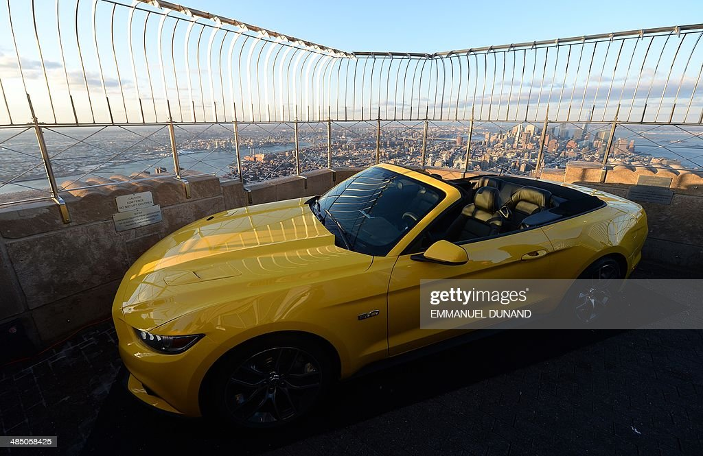 The 2015 Ford Mustang convertible is revealed at the top of the Empire State Building in New York, April 16, 2014. Fifty years ago, Ford Motors debuted its iconic Mustang at the 1964 World's Fair in New York City. To mark the occasion, the car company cut up one of its new cars into three pieces and reassembled it on the top of the Empire State building. In honor of the anniversary, the company has taken a prototype of the 2015 Mustang, cut into even more piece than the original 1964 car and ferried it to the top of the second largest building in the city. The newest model will be on display to visitors on April 16 and 17. AFP PHOTO/Emmanuel Dunand