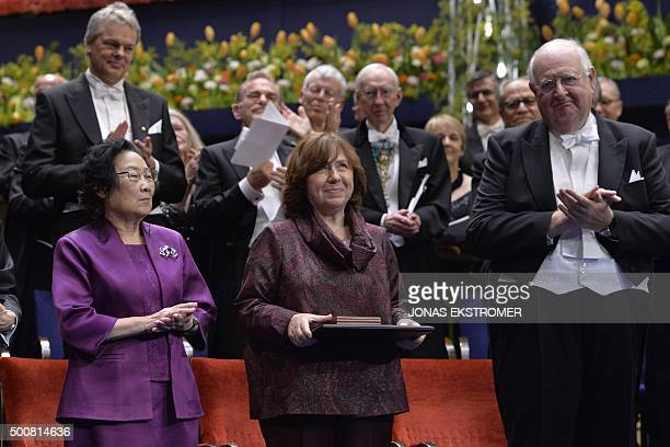 The 2015 Nobel literature laureate Svetlana Alexievich of Belarus is applauded by fellow laureates Tu Youyou and Angus Deaton during the 2015 Nobel...